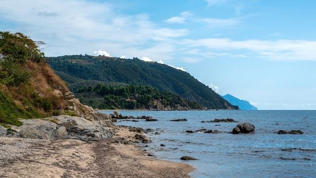 Côte de la mer égée à ouranoupolis avec des rochers dans l'eau en grèce