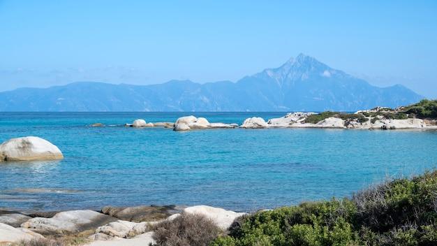 Côte de la mer égée avec des rochers sur l'eau et la terre au loin, la verdure au premier plan, l'eau bleue, la grèce