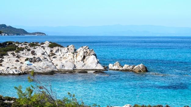 Côte de la mer égée avec de la verdure autour, des rochers et des buissons, de l'eau bleue et des gens au repos, grèce