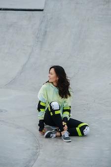 À côté de la patineuse brune en tenue de sport assise sur sa planche sur un sol en béton. long shot