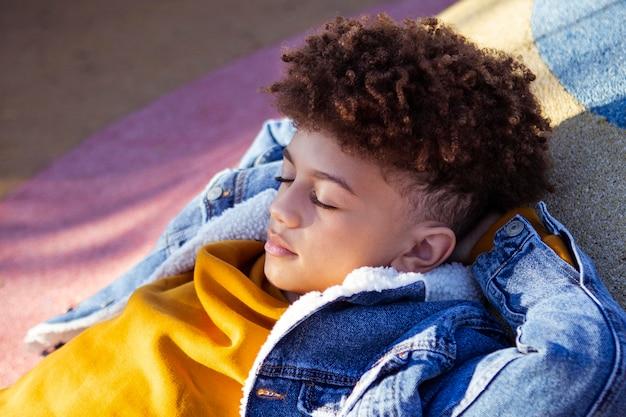 Sur le côté, petit garçon se détendre sur l'aire de jeux