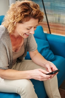 Côté portrait, de, femme souriant, chez soi, écriture, texte, sur, téléphone intelligent