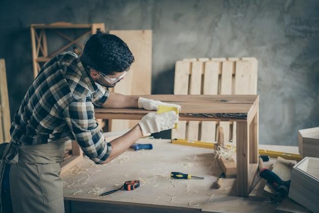 Côté profil, contremaître axé sur la restauration de la table de dalle polonaise surface en bois de sculpture lisse dans le garage de la maison