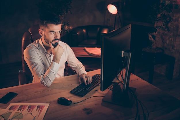 Côté profil du marketing concentré assis sur la table de travail de la nuit de l'ordinateur
