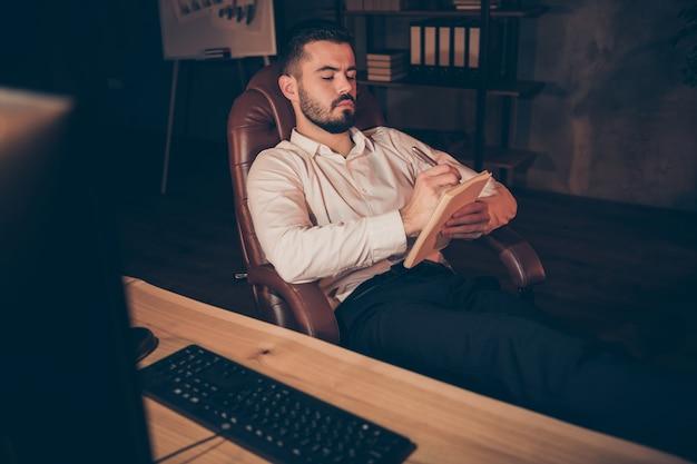 Côté profil de l'homme de brainstorming créatif assis fauteuil écrire dans un cahier