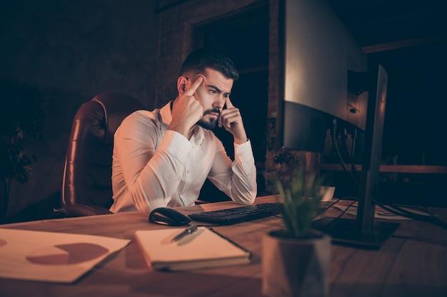 Côté profil de l'homme concentré s'asseoir table travail ordinateur pc temple doigts