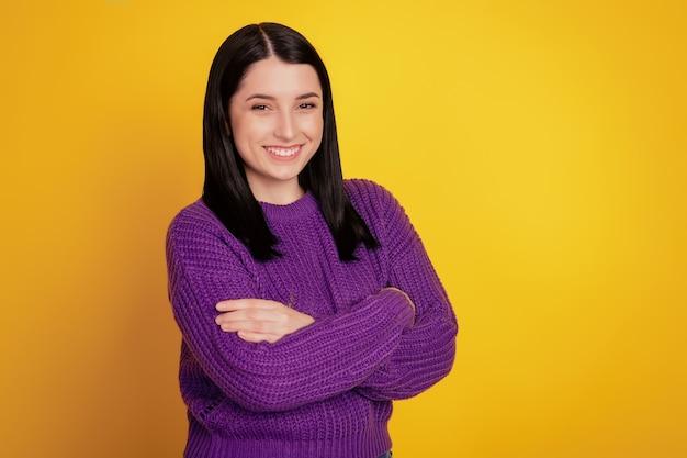 Côté profil photo de jeune femme joyeuse sourire positif heureux les mains croisées confiant isolé sur fond de couleur jaune