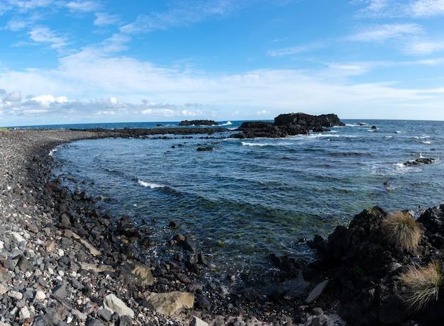 Côte rocheuse dans les açores. vagues éclaboussant sur des roches basaltiques