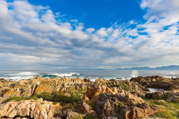 Côte rocheuse sur l'océan à de kelders, afrique du sud, célèbre pour l'observation des baleines. saison d'hiver, ciel nuageux et dramatique.