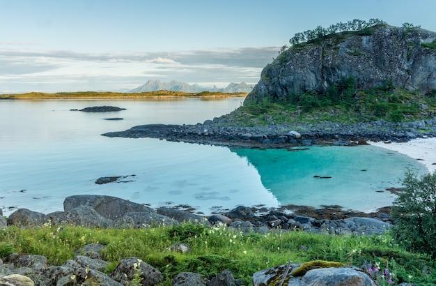 Côte rocheuse et une plage de sable près de l'îlot trollskarholmen, arstein, lofoten, norvège