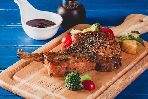 Côtelette de porc au steak avec légumes sur planche de bois