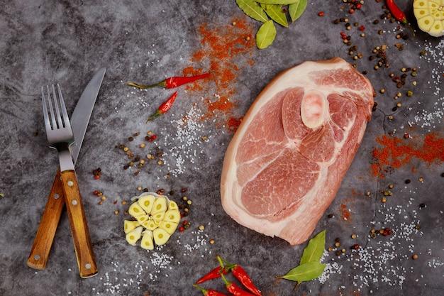 Côtelette de porc crue aux épices et couperet sur fond sombre. vue de dessus.