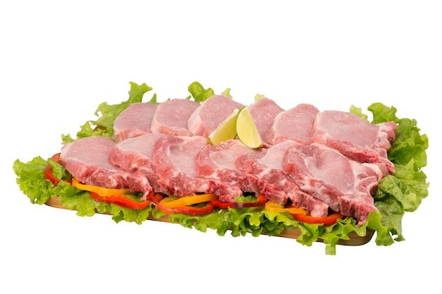 Côtelette de porc crue sur une planche à découper sur fond blanc.