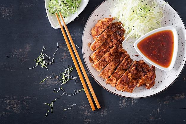 Côtelette de porc frite au chou et sauce tonkatsu.