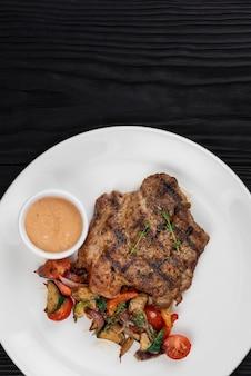 Côtelette de porc frite avec légumes grillés et sauce sur plaque blanche sur fond de bois noir