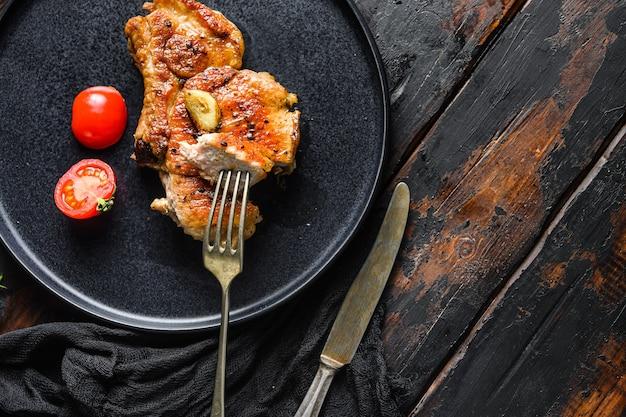 Côtelette de porc grillée avec vue de dessus de tomates avec couteau et tranche sur une fourchette sur un espace de vue de dessus de plat noir pour le texte sur fond de bois.
