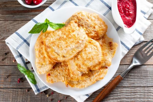 Côtelette de poulet frit. côtelette de poulet frite maison sur une table en bois avec sauce aux baies. style rustique. fermer. vue de dessus