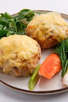 Côtelette recouverte de fromage fondu servie avec carotte fraîche, oignon nouveau et parsey