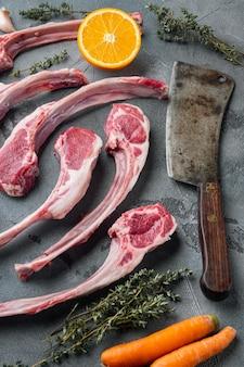 Côtelettes d'agneau crues ou ensemble de coupes de mouton, avec des ingrédients orange carotte, herbes et vieux couteau de couperet de boucher, sur fond de pierre grise