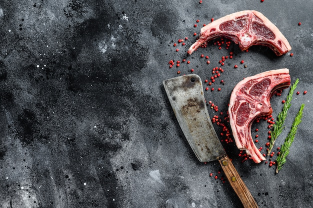 Côtelettes d'agneau crues fraîchement coupées avec couperet à viande.