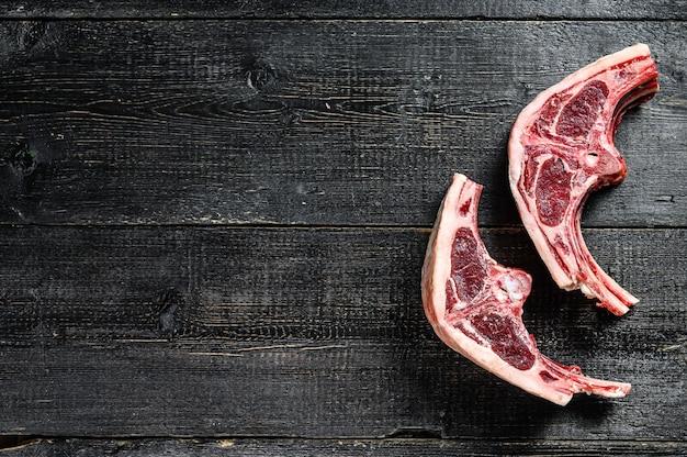 Côtelettes d'agneau crues fraîchement coupées. fond noir