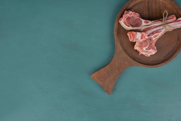 Côtelettes d'agneau crues sur planche de bois.
