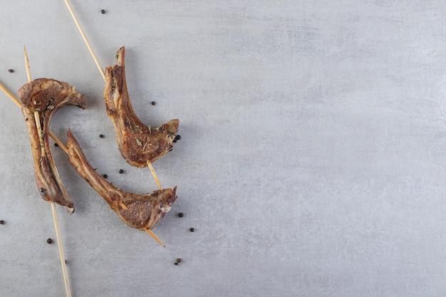 Côtelettes d'agneau frites avec des bâtons placés sur une table en pierre.