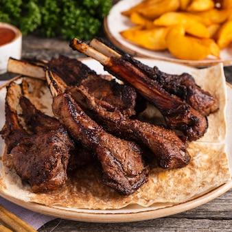 Côtelettes d'agneau grillées sur une assiette. mouton sur un gril. fermer