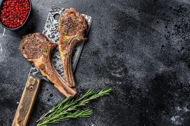 Côtelettes d'agneau grillées au barbecue sur un couperet à viande de boucherie
