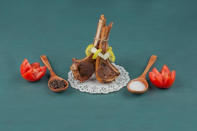 Côtelettes d'agneau grillées avec des grains de sel et de poivre sur table bleue.