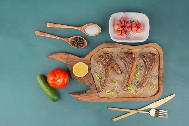 Côtelettes d'agneau grillées sur planche de bois avec des légumes.