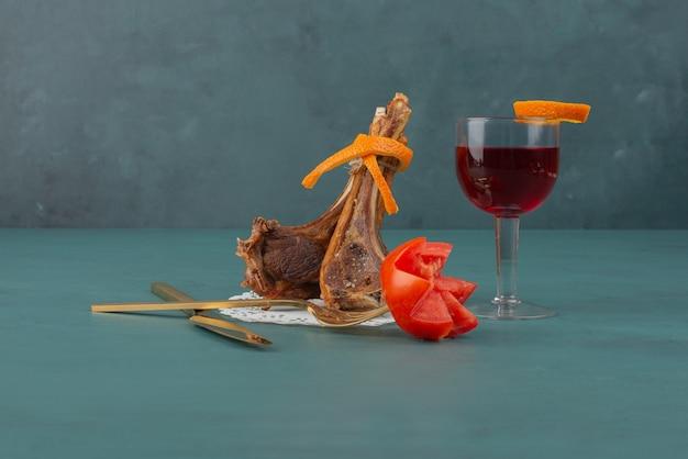 Côtelettes d'agneau grillées et un verre de jus sur table bleue.