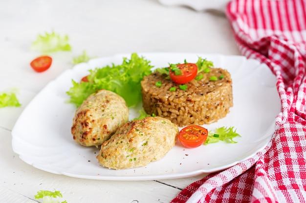Côtelettes au four faites maison avec du riz sur une table dans un style rustique. la nourriture saine