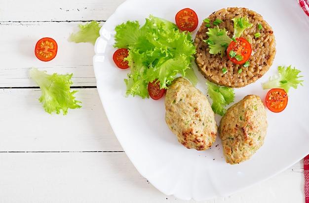 Côtelettes au four faites maison avec du riz sur une table dans un style rustique.