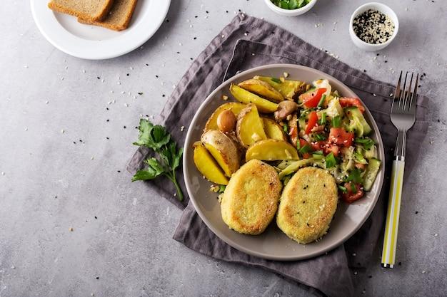 Côtelettes cuites, pommes de terre au four et salade de légumes, assiette grise et serviette sur fond gris
