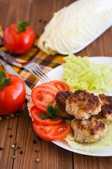Côtelettes frites et légumes frais sur une table en bois