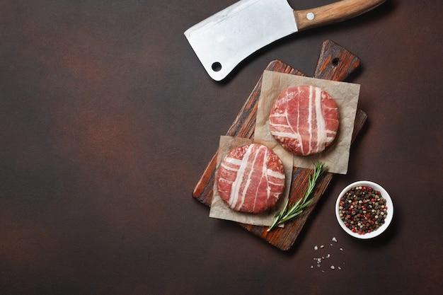 Côtelettes d'hamburger crues au romarin sur une planche à découper et fond rouillé
