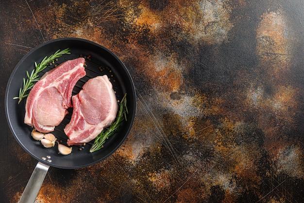 Côtelettes de longe de porc cru sur un os dans une poêle à frire noire sur une vieille surface métallique sombre rustique romarin ail en grains de poivre vue de dessus espace pour le texte