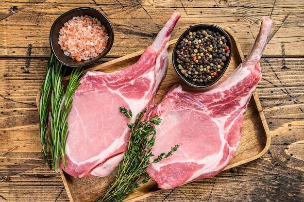 Côtelettes de longe de porc crues fraîches avec du poivre et du sel. fond en bois. vue de dessus.