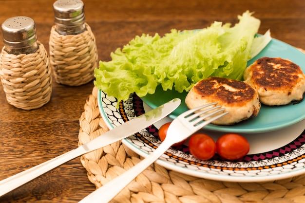 Côtelettes maison juteuses (boeuf, porc, poulet) sur un fond en bois.
