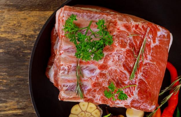 Côtelettes de porc sur les côtes crues, prêtes à être grillées.