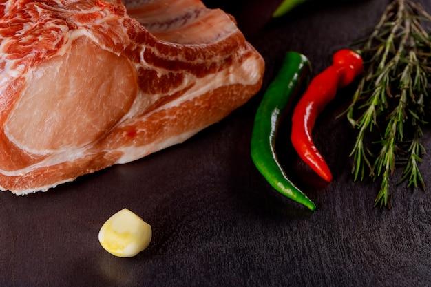 Côtelettes de porc cru avec des herbes et des épices sur une planche à découper. prêt pour la cuisine.