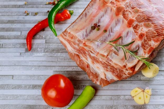 Côtelettes de porc crues avec œil avec os et épices sur des planches à découper.