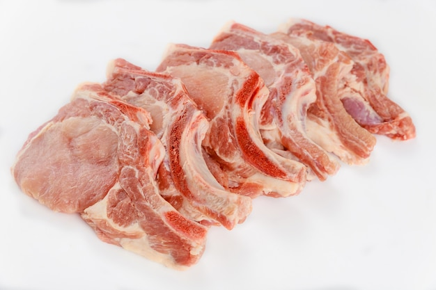 Côtelettes de porc crues en os isoladet sur fond blanc.