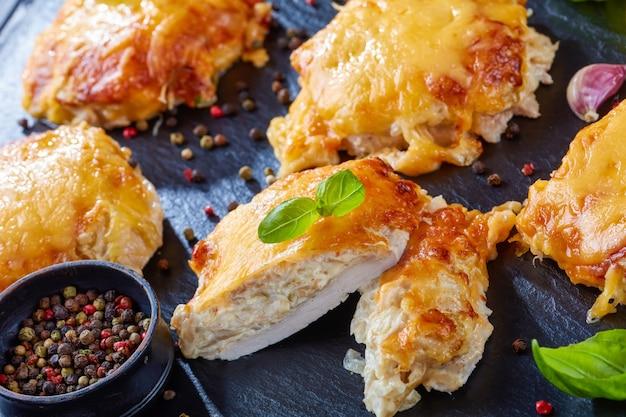 Côtelettes de porc garnies d'oignons finement hachés, mayonnaise et fromage fondu sur une plaque d'ardoise noire sur une table en bois, vue d'en haut, gros plan