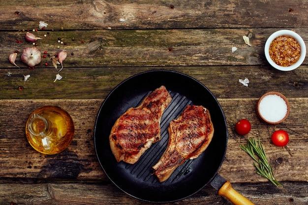 Côtelettes de porc grillées dans une assiette avec une fourchette et un couteau sur une vieille table en bois.