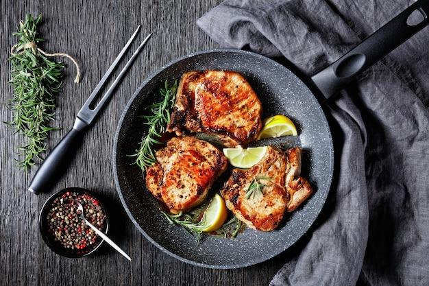 Côtelettes de porc rôties avec des brins de romarin et des tranches de citron dans une poêle sur une table en bois, vue horizontale d'en haut, mise à plat