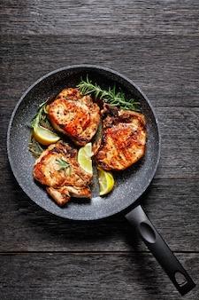 Côtelettes de porc rôties, karbonade avec brins de romarin et tranches de citron dans une poêle sur une table en bois, vue horizontale d'en haut, mise à plat