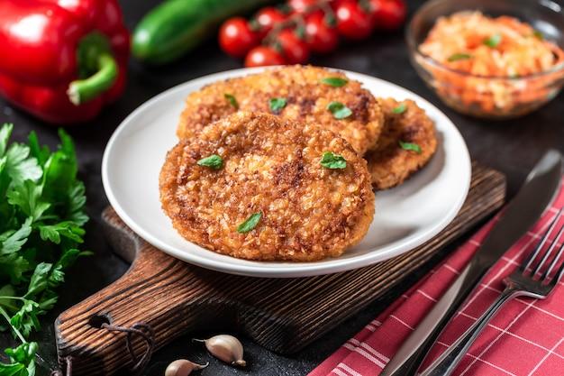 Les côtelettes se trouvent sur une assiette blanche. les côtelettes de poulet se trouvent parmi les légumes sur une table en pierre noire.