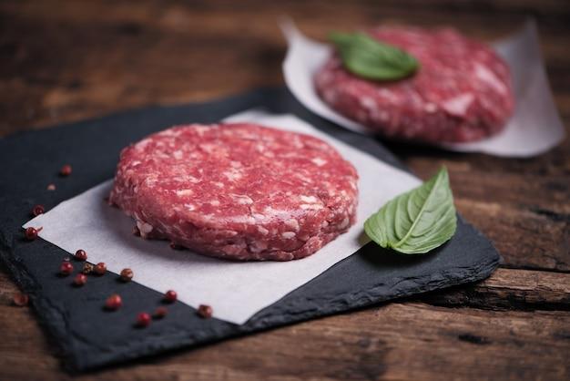Côtelettes de steak de hamburger de viande de boeuf haché crue sur fond de bois se bouchent